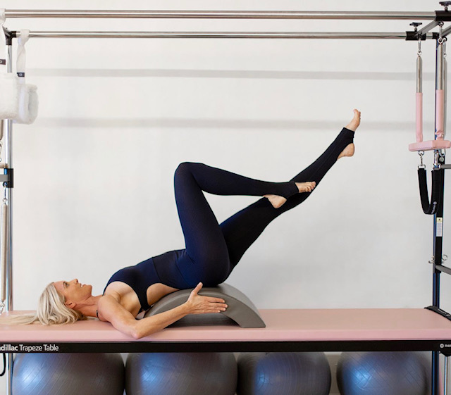 woman in pebbles pilates jumpsuit on cadillac reformer
